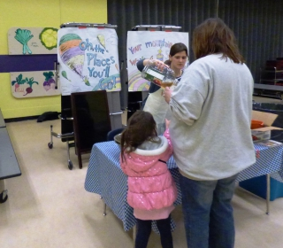Farm to School Coordinator Rachel Sacco serves up smoothies and juice at Read Across America night.