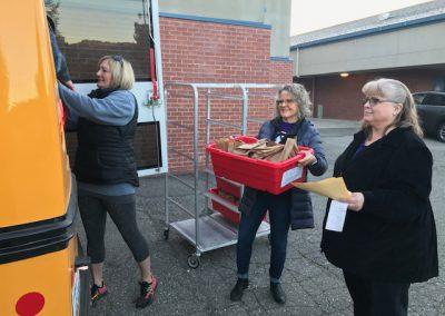 Jaci Gallagher, Cheri VanWagoner, & Marla Reed load meals into a bus.