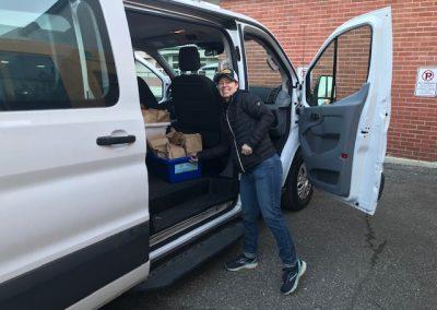 Stephanie Henning loading a meal onto a school vehicle.
